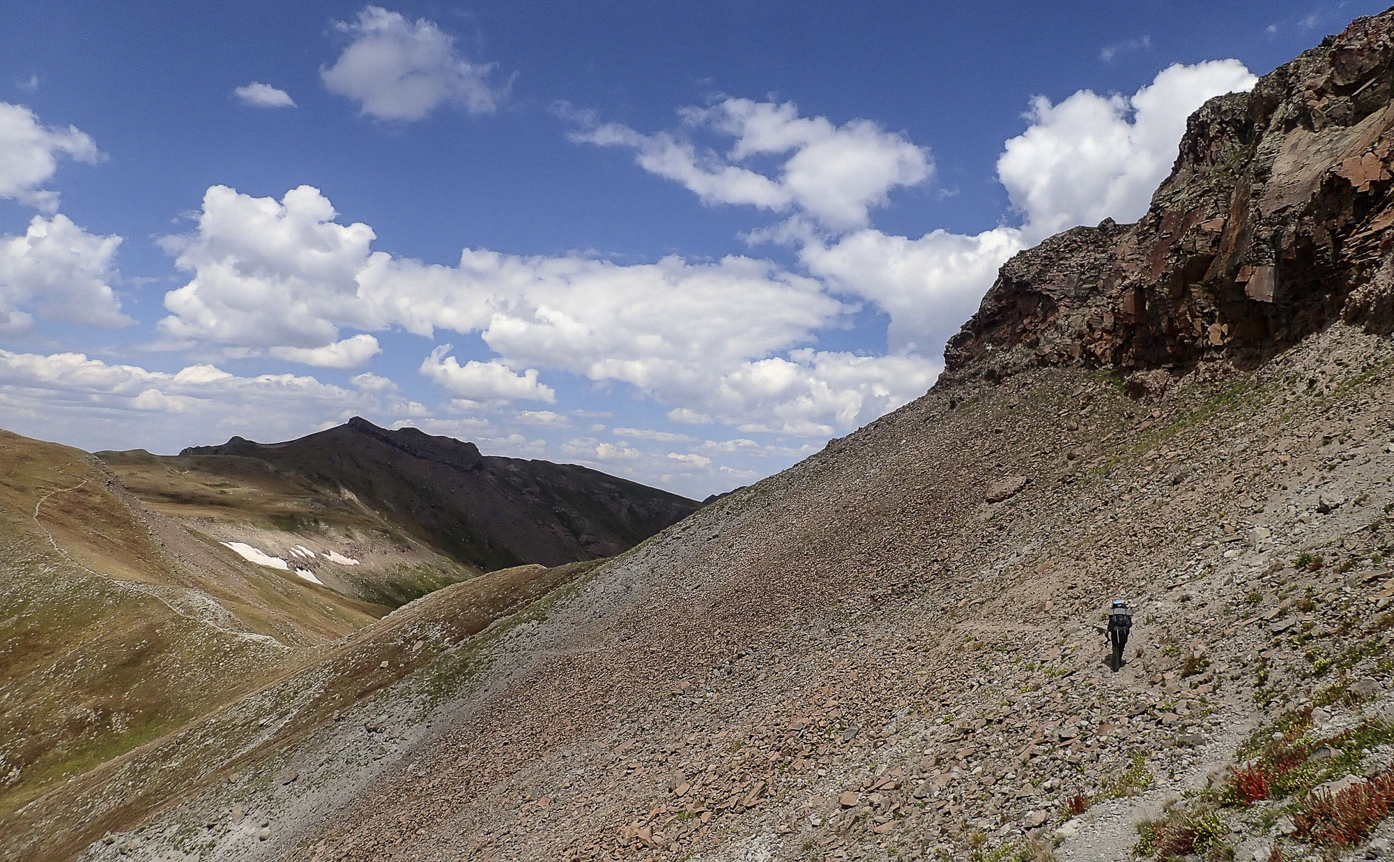 A hiker on a scree field in the Collegiate Range