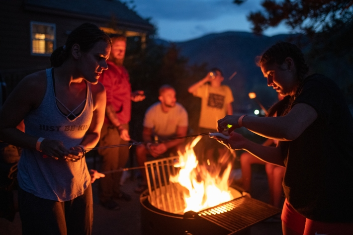 A campfire illuminates Rebeca Wenzel, 40, left, of Mesa, Ariz., as she helps make a s'more for her niece Kayla Barreto, 21, of Huntley, Ill., while camping with their families and others at Yogi Bear's Jellystone Park Camp-Resort of Estes on June 29, 2019 near Estes Park. For seven years running, members of the Wenzel, Barreto and Munn families have gathered together at Jellystone resorts for an annual retreat. This year they rented four cabins for several days following a family member's wedding nearby. Photo by Andy Colwell, special to the Colorado Sun