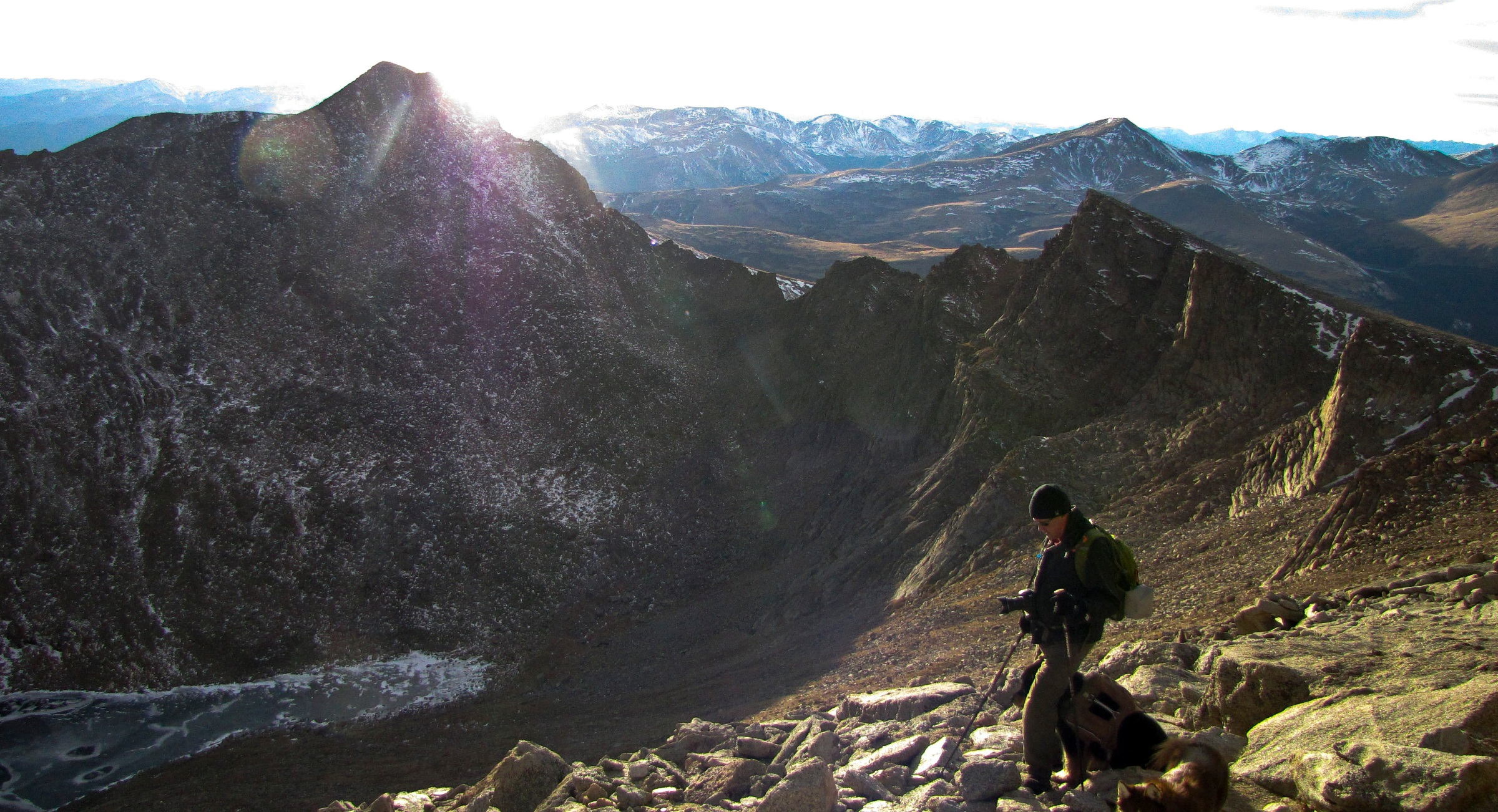 A climber admires the view from near the summit of Mount Evans in Colorado. Mount Evans, in the Mount Evans Wilderness, is 14,265' in elevation and the 12th highest peak in Colorado. Although a paved road, State Highway 103,climbs the mountain and stops just below the summit there are many challenging routes for climbers. This photo was taken after an ascent on Mount Evan's West Ridge. Evans was originally named Mount Rosalie but was changed to Evans in 1895 for John Evans, the 2nd governor of Colorado who resigned for his part in the Sand Creek Massacre. (Dean Krakel, Special to The Colorado Sun)