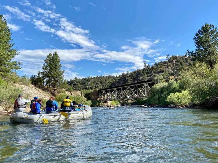 Rafters float the Arkansas River into Browns Canyon National Monument below a railroad bridge. A billionaire farmer on the Eastern Plains promises he will donate a 60-mile right-of-way along the track if he is able to run trains on the dormant line. (Jason Blevins, The Colorado Sun)