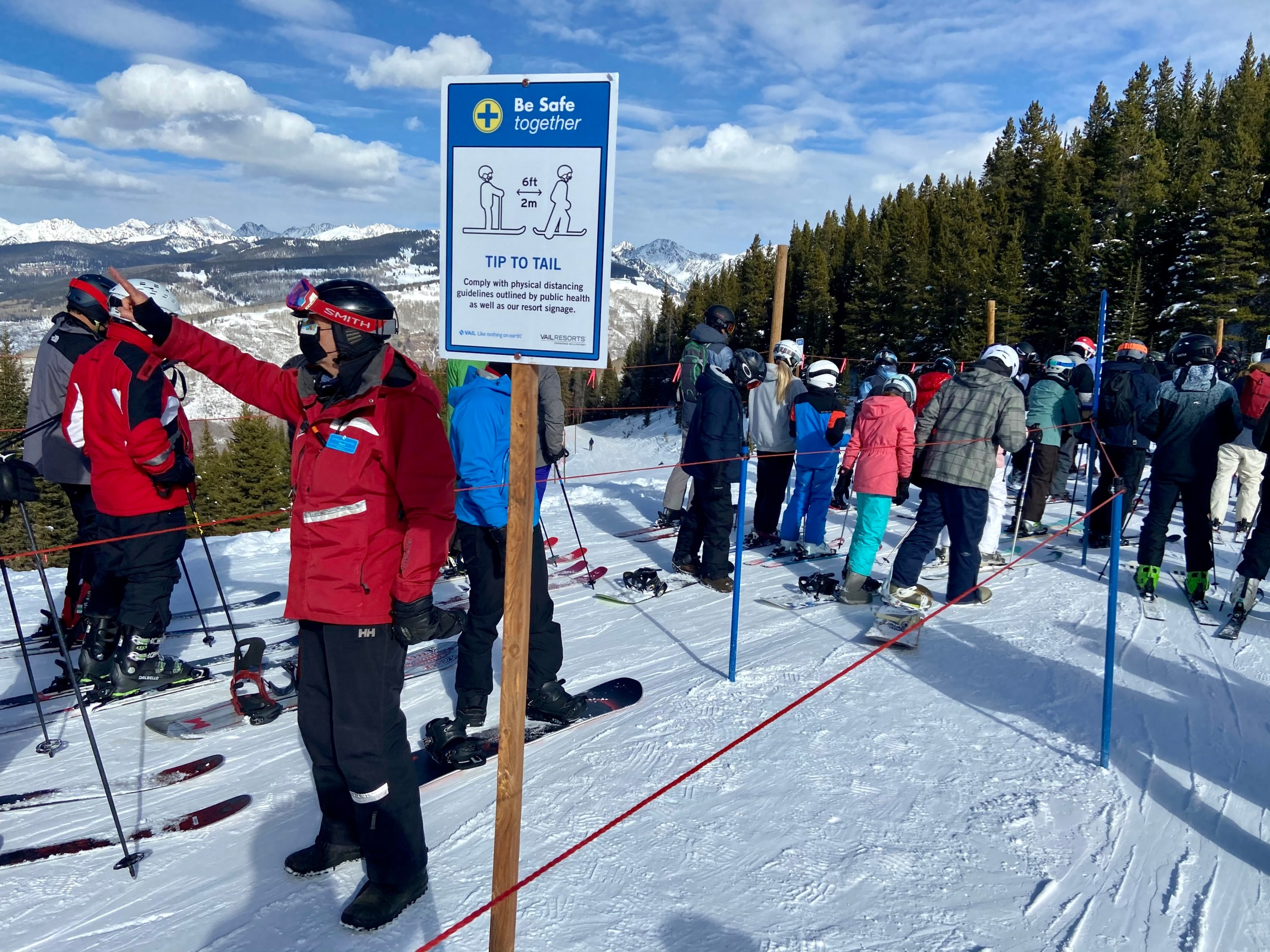 A Vail employee in an empty lane between lines of skiers reminds skiers to keep their masks over their nose. (Jason Blevins, The Colorado Sun)