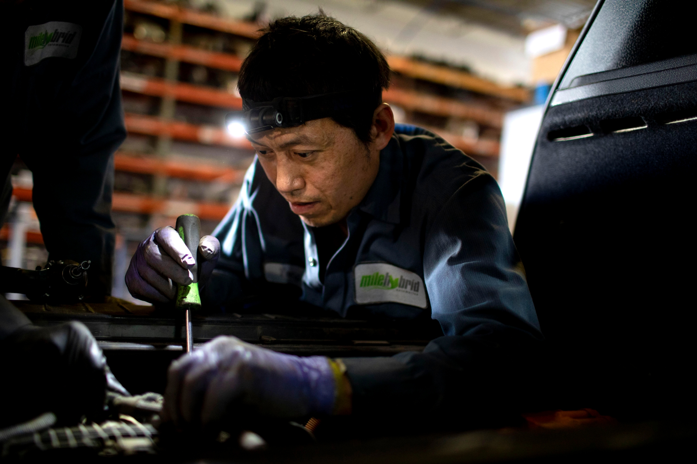 A technician dissembles an EV battery compartment.