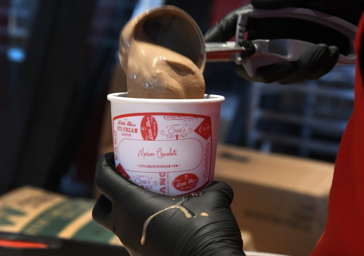 At Little Man Ice Cream Factory Assistant, production manager Argeni Hau scoops Mexican Chocolate ice Cream into pint containers on August 3, 2021 in Denver, Colorado.