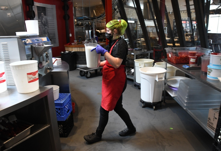 Production lead Maeve Wenglewick carries ingredients to the ice cream maker as she works to make nine gallons of strawberry ice cream at Little Man Ice Cream Factory on August 3, 2021.